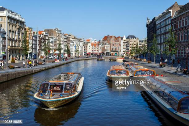 bicycles, boats and amsterdam canal - tourboat stock pictures, royalty-free photos & images