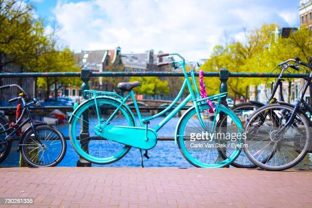 Bicycles By Water In City Against Sky