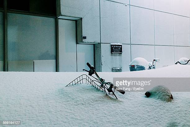 Bicycles Covered In Snow Against Building
