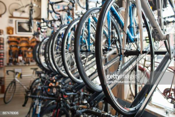 bicycles hanging on rack in store - jetta productions stock pictures, royalty-free photos & images