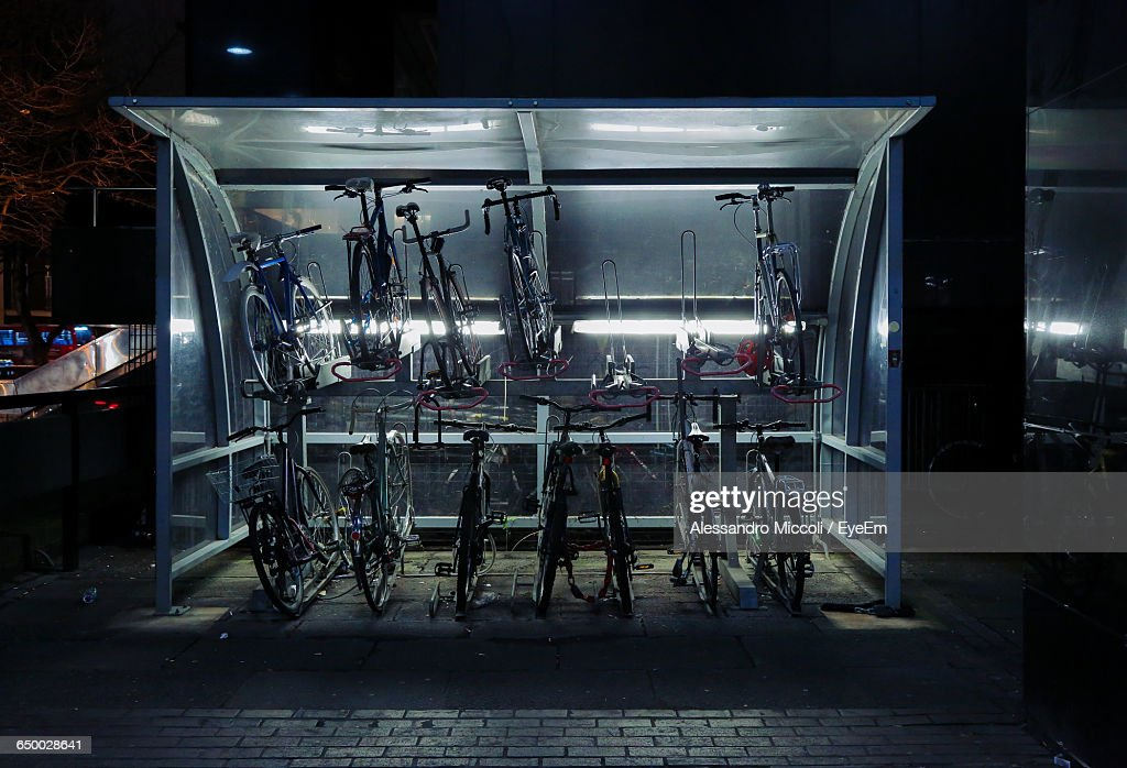 Bicycles In Illuminated Parking Lot At Night : Stock Photo