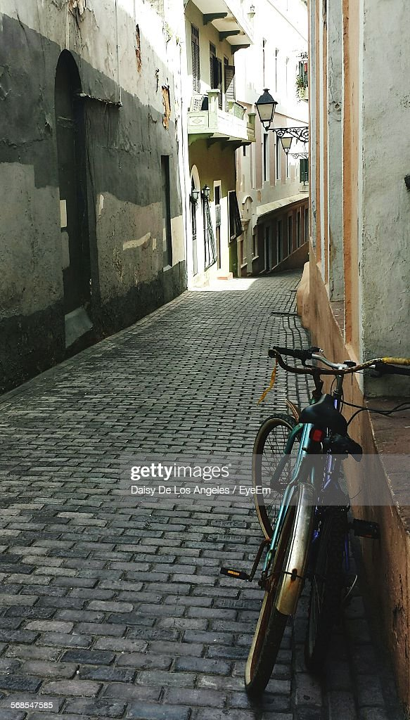 Bicycles Leading On Wall In Alley : Stock Photo