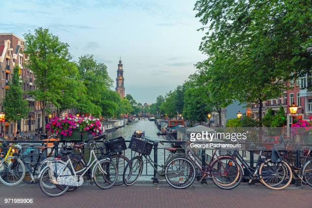 bicycles on a bridge in prinsengracht canal, amsterdam - holanda fotografías e imágenes de stock