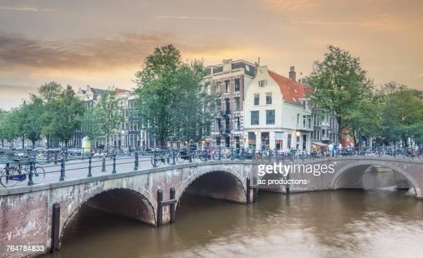 bicycles on bridge over urban river - noord holland stockfoto's en -beelden