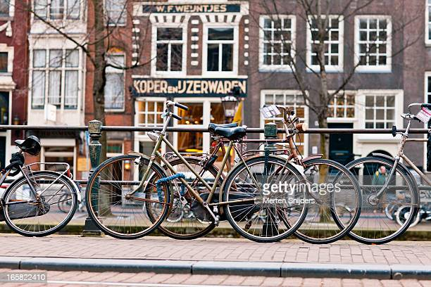 bicycles parked along herengracht canal - merten snijders stock pictures, royalty-free photos & images