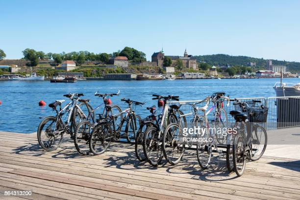 bicycles parked at aker brygge in oslo, norway - bicycle parking station stock photos and pictures