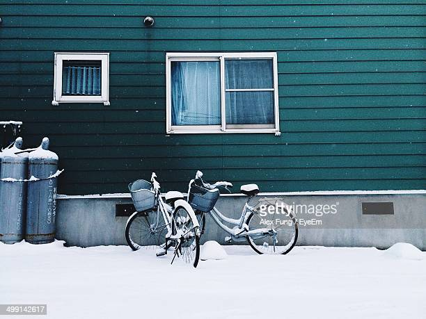 Bicycles parked by house in snow