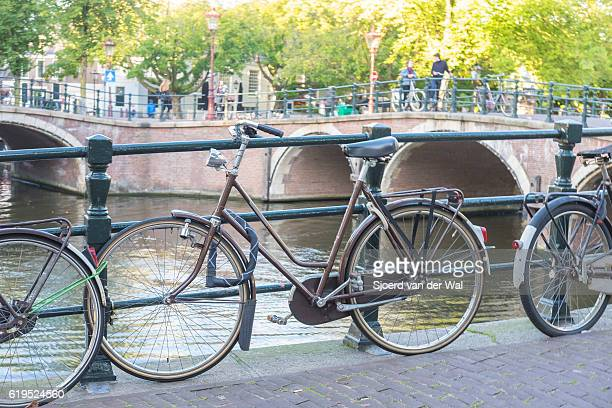 "bicycles parked next to a canal in amsterdam, the netherlands - ""sjoerd van der wal"" fotografías e imágenes de stock"