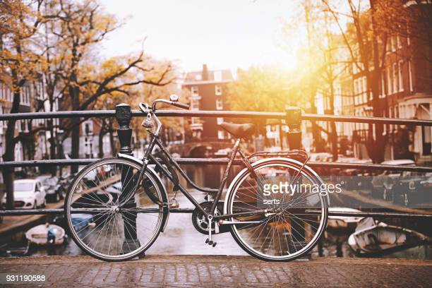 bicycles parked on a bridge in amsterdam - amsterdam stock pictures, royalty-free photos & images