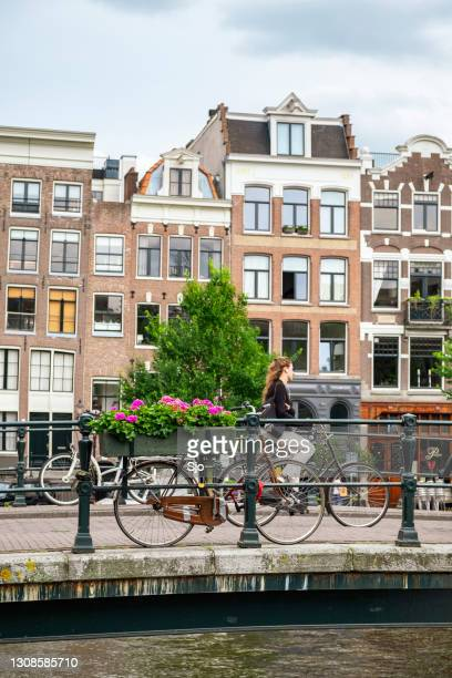 """bicycles parked on a bridge overa canal in amsterdam with a woman cycling over the. bridge - """"sjoerd van der wal"""" or """"sjo"""" stock pictures, royalty-free photos & images"""