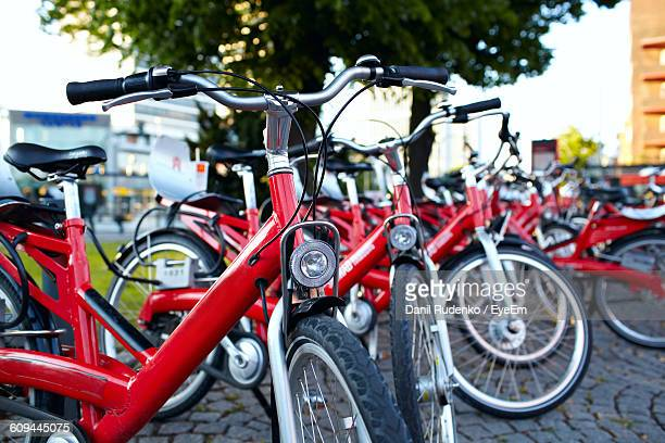 Bicycles Parked On Cobblestone Street Against Trees