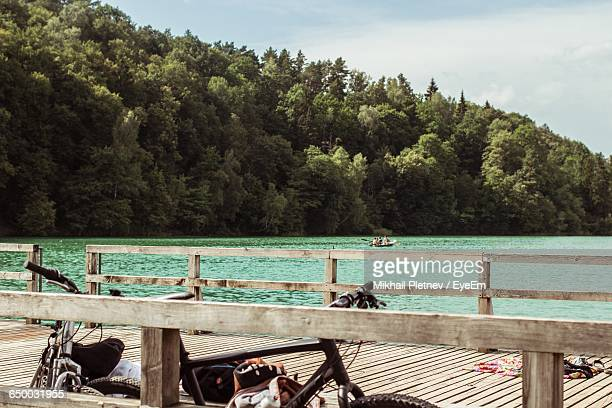 bicycles parked on pier over lake by forest - human powered vehicle fotografías e imágenes de stock