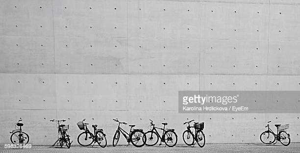 Bicycles Parked On Sidewalk Against Wall In City