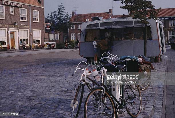 Bicycles parked outside a french fry stand in a public square, with a cafe and a Stella Artois beer advertisement, Holland, 1960. .