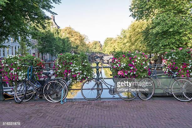 bicycles parkes on a bridge in amsterdam - kanal stock-fotos und bilder
