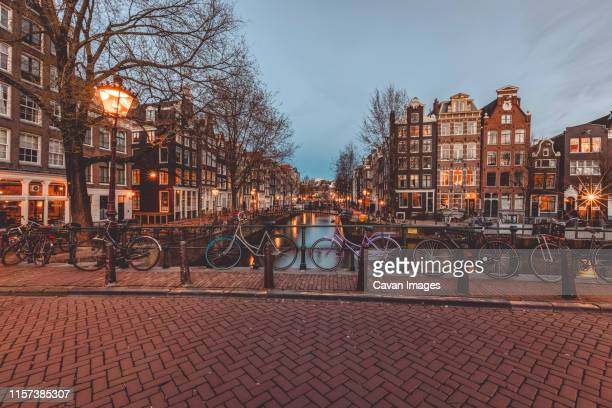 bicycles standing on bridge on water canal in old town of amsterdam. - amsterdam stock pictures, royalty-free photos & images