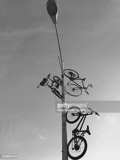 Bicycles Tied On Street Light Pole Against Sky