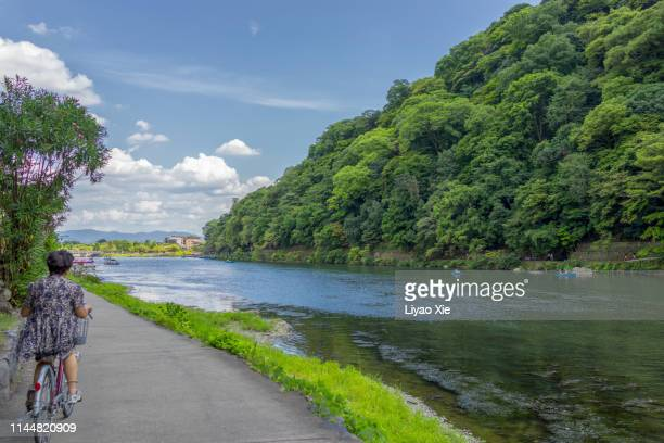 bicycling along the river - liyao xie stock pictures, royalty-free photos & images