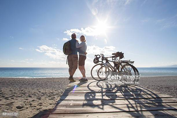 Bicycling couple look out to sea from beach wharf