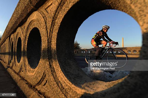 A bicyclist is framed as they cross the Inlet Bridge between the Tidal Basin and Potomac River as the sun and warmer temperatures help melt the...