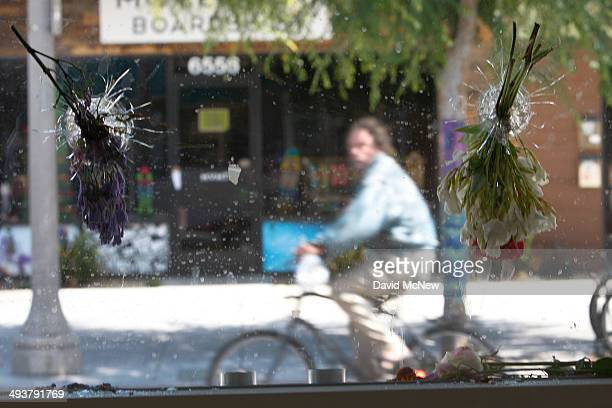 A bicyclist is seen passing behind flowerfilled bullet holes in the windows of the IV Deli May 25 2014 in Isla Vista California According to reports...