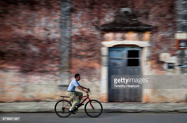 bicyclist on street with colonial building beyond - timothy hearsum stockfoto's en -beelden