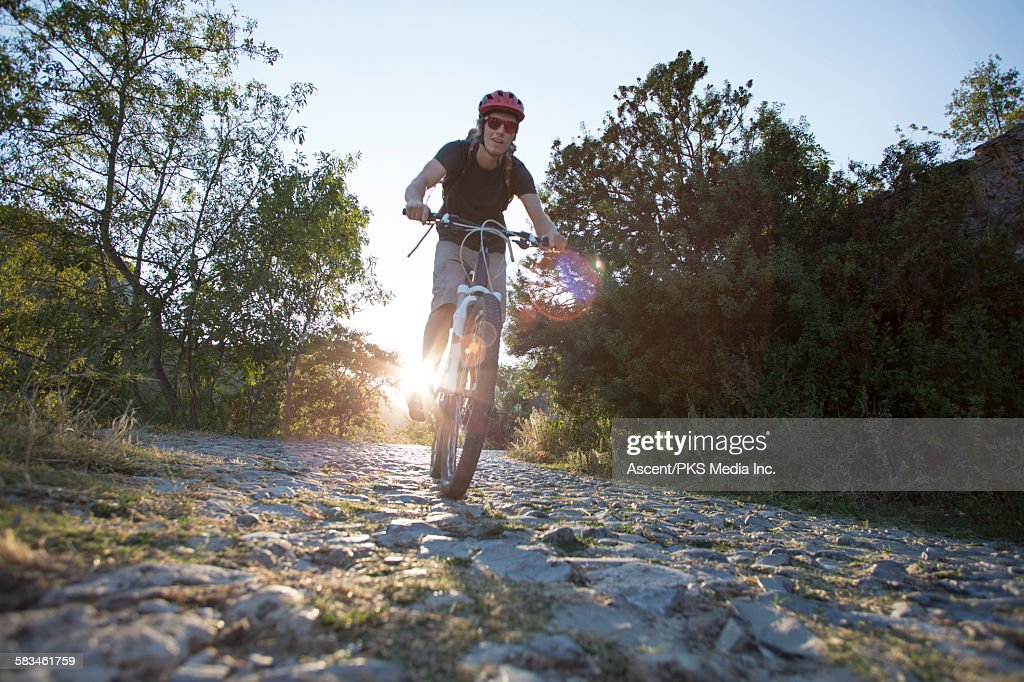 Bicyclist peddles down cobblestone path, sunrise : Stock Photo