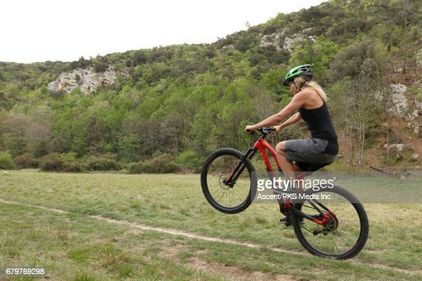 bicyclist pops wheelie on forest trail - leanincollection stock pictures, royalty-free photos & images
