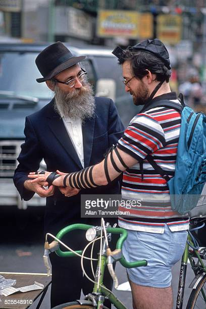 A bicyclist puts on tefillin with the help of an orthodox rabbi at the Lower East Side Jewish Festival New York New York June 17 1986