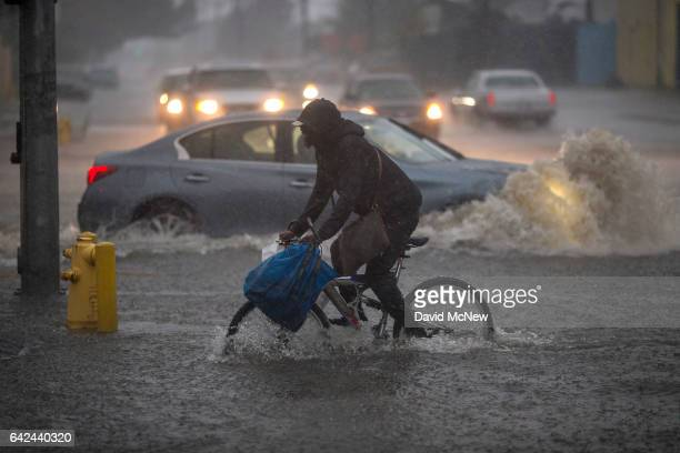A bicyclist rides along a flooded street as a powerful storm moves across Southern California on February 17 2017 in Sun Valley California After...