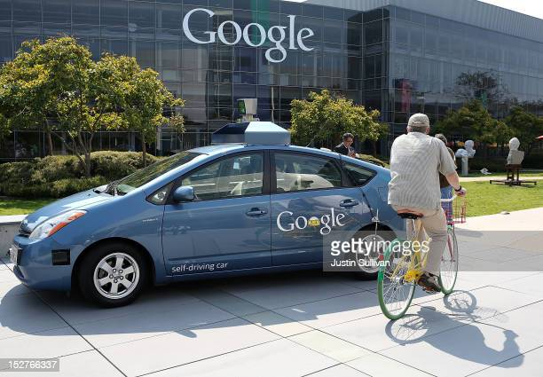 A bicyclist rides by a Google selfdriving car at the Google headquarters on September 25 2012 in Mountain View California California Gov Jerry Brown...