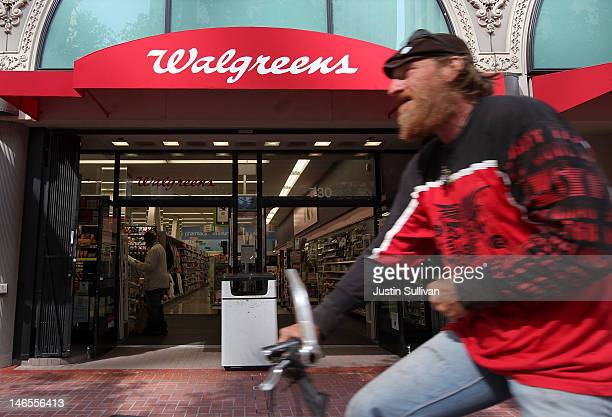 A bicyclist rides by a Walgreens store on June 19 2012 in San Francisco California US based drug store chain Walgreens has announced a deal to...