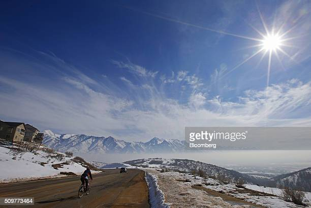 A bicyclist rides down Traverse Mountain into Utah County that is filled with smog from a winter temperature inversion in Draper Utah US on Wednesday...
