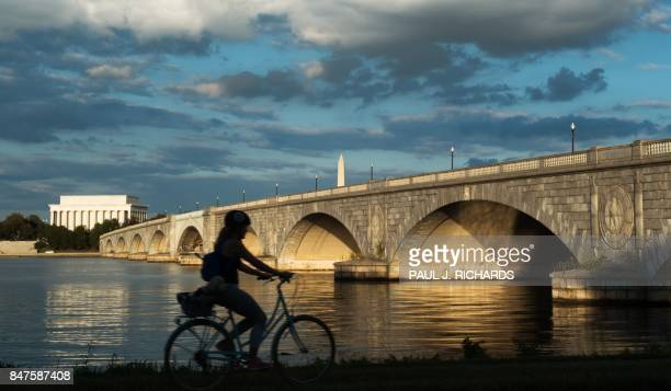 A bicyclist rides during sunset along the Mt Vernon Trail that follows the Potomac River in Virginia near the Arlington Memorial Bridge the Lincoln...