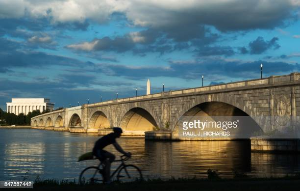 TOPSHOT A bicyclist rides during sunset along the Mt Vernon Trail that follows the Potomac River in Virginia near the Arlington Memorial Bridge the...