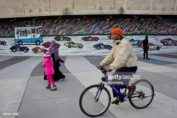 A bicyclist rides past a family walking in front of a mural painted along the Detroit River Walk in downtown Detroit Michigan US on Sunday Oct 4 2015...