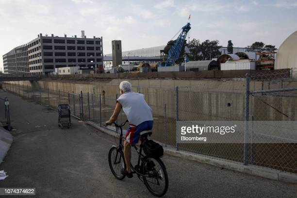 Bicyclist rides past equipment at the Boring Co. Test tunnel across from Space Exploration Technologies Inc. In Hawthorne, California, U.S., on...