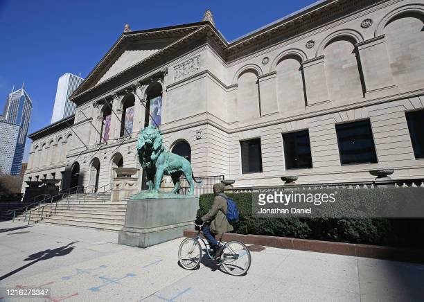 "Bicyclist rides past the shuttered Art Institute of Chicago during the ""shelter in place"" order that was continued until April 30 for the COVID-19..."