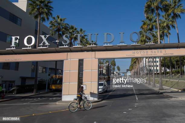 A bicyclist rides through the main entrance to Fox Studios after the Walt Disney Company announced that it will acquire 21st Century Fox on December...