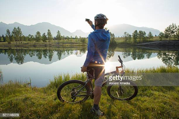 Bicyclist takes smart phone pic of mountains, lake