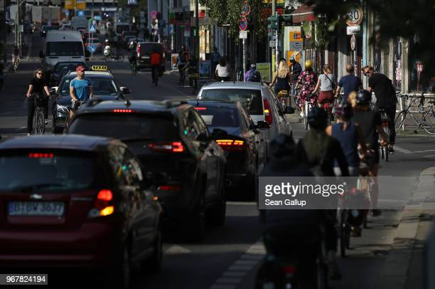Bicyclists and cars drive in the city center on June 5 2018 in Berlin Germany Bicycles are a popular alternative to other forms of transportation in...