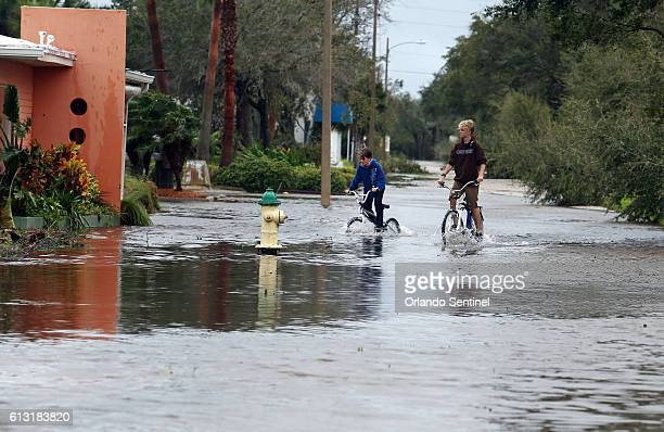 Bicyclists make their way through a flooded street as heavy rains from Hurricane Matthew cause flooding Thursday Oct 7 2016 in New Smyrna Beach Fla...