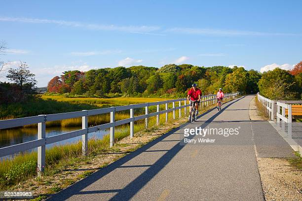 Bicyclists on path through salt marsh, Falmouth