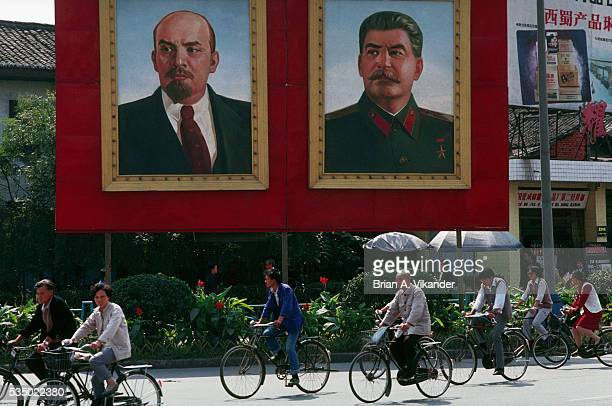 Bicyclists Pass Murals of Lenin and Stalin