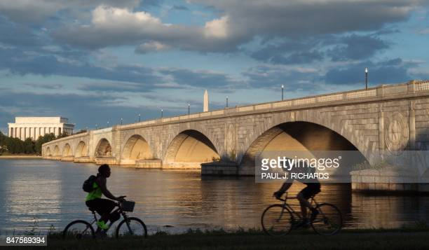 Bicyclists ride along the Mt Vernon Trail that follows the Potomac River in Virginia near the Arlington Memorial Bridge the Lincoln Memorial and the...
