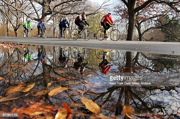 Bicyclists riding along the loop in Prospect Park are reflected in a puddle as the weather in the city continues to be unseasonably warm