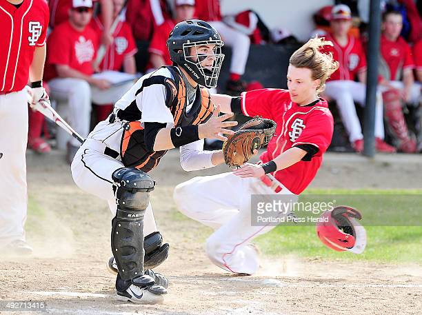 Biddeford catcher #14 Corey Brown waits for the ball from deep center field as South Portland Cosmo Ramano slides safely home for the team's fourth...
