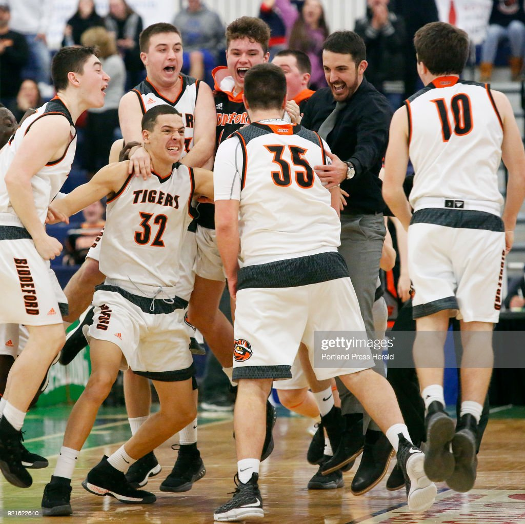 Biddeford vs Brunswick boys Class A quarterfinal. Biddeford teammates and coaches rush the court to celebrate with Zachary Reali (#35) who hit a buzzer beater to lift the Tigers over Brunswick.
