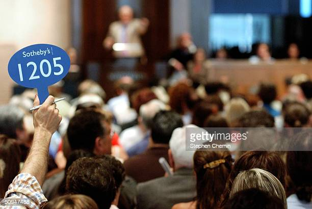 A bidder holds up his bidding sign during the Katharine Hepburn auction at Sotheby's June 10 2004 in New York City Property from the estate of the...
