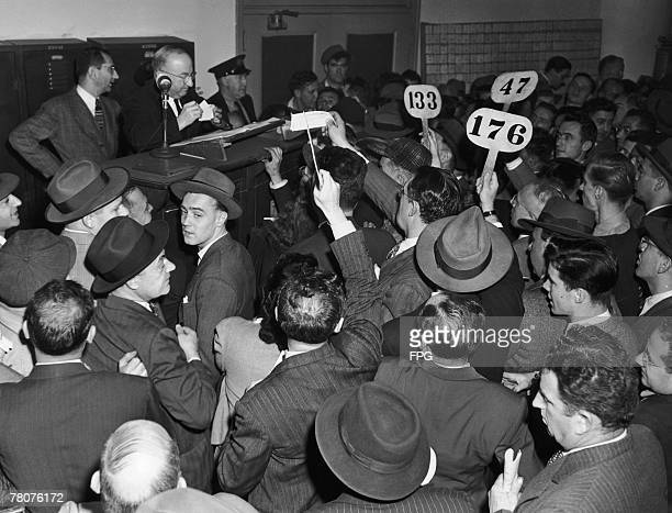 Bidders at an auction of cars being sold off by the US government circa 1950